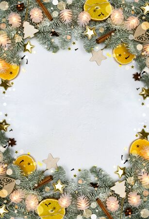 Christmas tree vertical holiday frame, decor, garland lights, creative soft bokeh on white snow background with copy space. Frosty fir, dry orange, spice, cinnamon, badian, wooden toy, star confetti