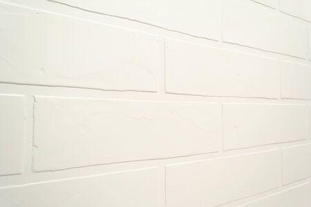 Sfondo muro di mattoni bianchi. Chiuda sulla struttura interna moderna di Indor. Costruzione di superficie, muratura ad angolo concetto. Riparazione fai da te in stucco fatto a mano, imitazione della pietra naturale. Stucco per pareti, pittura