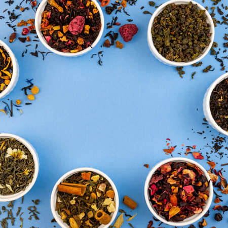 Assortment of dry tea in bowls on blue background. Flat lay square border template, copy space. Top view organic drink. Red, fruit, green, black and herbal leaves dried fresh dessert beverage. Reklamní fotografie