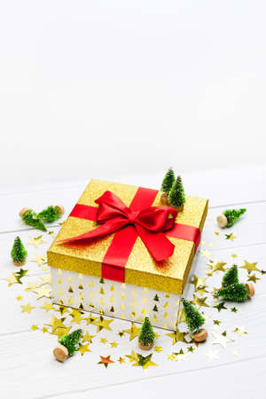 Golden present with red ribbon, stars confetti and toy decorative Christmas trees on white background. Sparkle new year decor. Holiday winter surprise banner template. Fairy tale magic still life