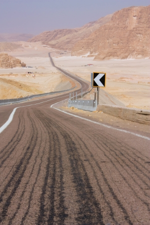 one lane street sign: road, leaving a zigzag into the distance, in the desert Stock Photo