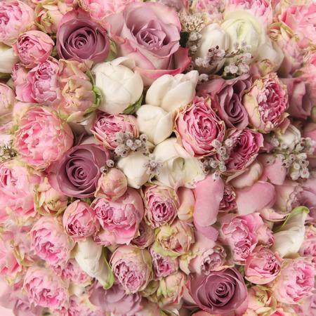 bruilofts -: bruidsboeket met rozenstruik, Ranunculus asiaticus als achtergrond