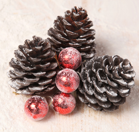 pine three: three snow-covered pine cones and red Christmas balls Stock Photo