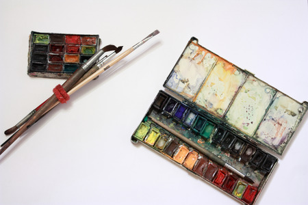 paintbox: well-used paintbox and brushes in over white  Stock Photo