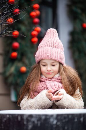 cute girl in winter clothes sculpts snowballs