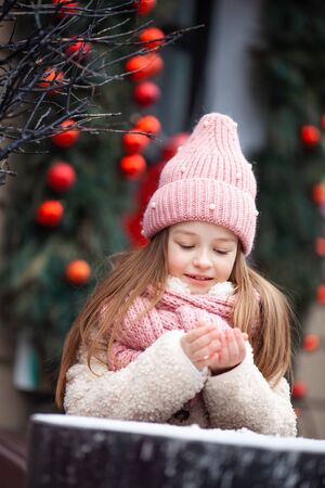 girl in winter clothes sculpts snowballs