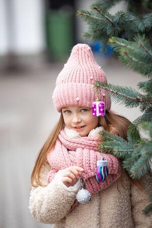 beautiful girl decorate a street tree with Christmas toys Zdjęcie Seryjne