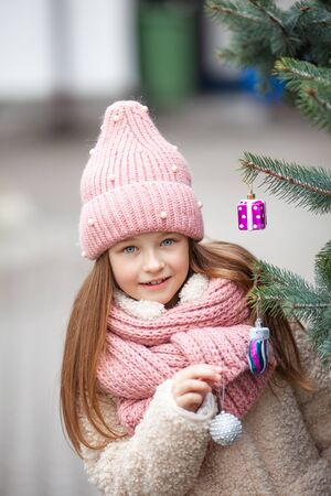 girl in winter clothes decorates a street Christmas tree Zdjęcie Seryjne