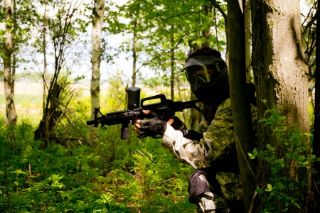 men playing paintball in forest