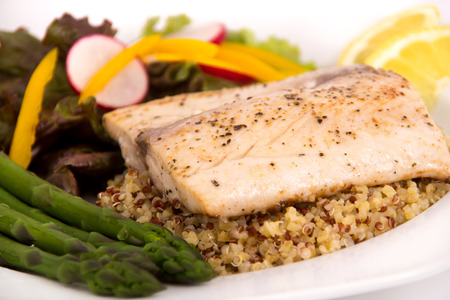 cooked mahi mahi fish fillet dish on quinoa with vegetables