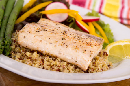 cooked mahi mahi fish fillet dish on quinoa with vegetables photo