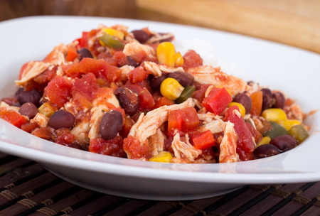 mexican chili chicken stew bowl, with black beans, pepper and tomato