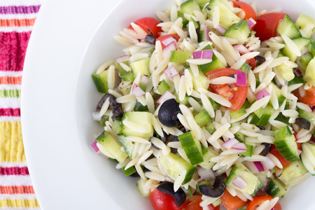 Mediterranean greek orzo pasta salad with black olives, red onion and cucumber