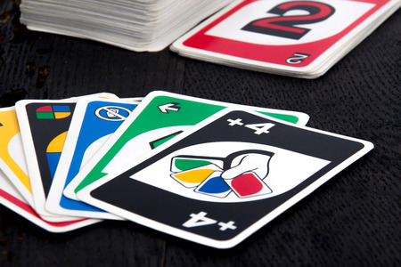 SorelTracy Canada May 25 2015: view of Uno card game black on wood table. The game was developed by Merle Robbins in Ohio USA in 1971 it is a Mattel product since 1992.