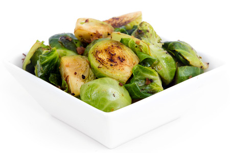 Roasted brussels sprouts with bacon over white background