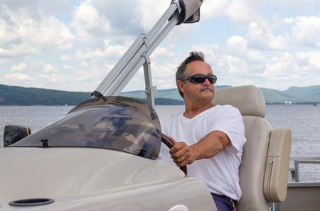 uomini maturi: uomini maturi in pensione alla guida di una barca pontone su un lago di giorno Archivio Fotografico