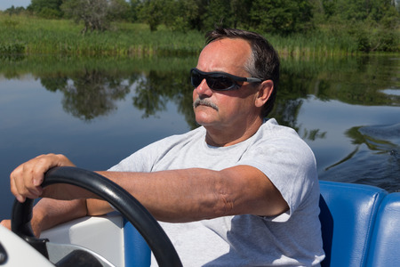 uomini maturi: uomini maturi di guida motoscafo in un fiume
