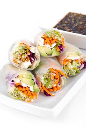 soy sprouts: colourful chicken, sprouts and avocado rice paper spring rolls with soy base dip sauce over white background
