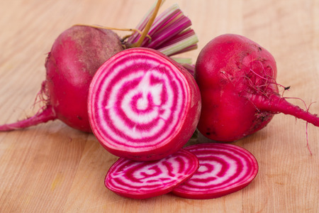 bullseye: Chioggia striped or candy stripe beet  whole and sliced on wood table