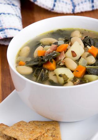 potato soup: white bean bacon and kale soup bowl closeup Stock Photo