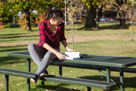 Women studying school book outdoor at fall at daytime