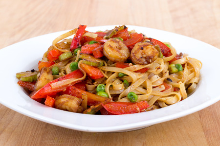 food on table: Shrimp stir fried with pasta and red bell pepper in a bowl