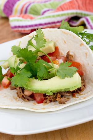 comida gourmet: tirada de cerdo taco suave con aguacate y cilantro