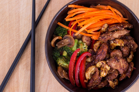 asian culture: asian culture sesame chicken bowl with vegetables and cashew closeup