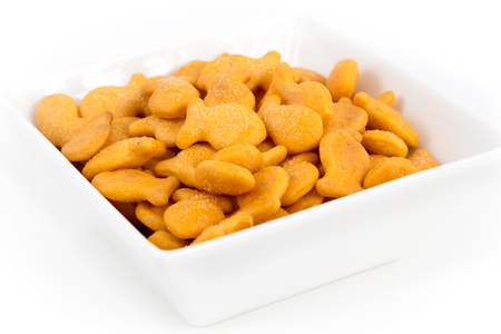 fish shaped cheddar crackers bowl over white background