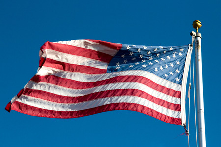 USA Flag waving in the wind on blue sky