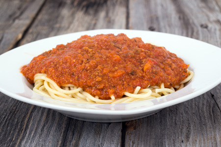 spaghetti with tomato and meat sauce plate on wood table