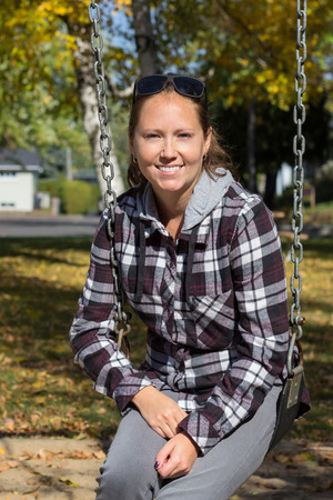 25 years old: smiling women on a swing at fall