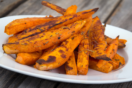 Sweet potato fries wedges closeup on wooden table Imagens