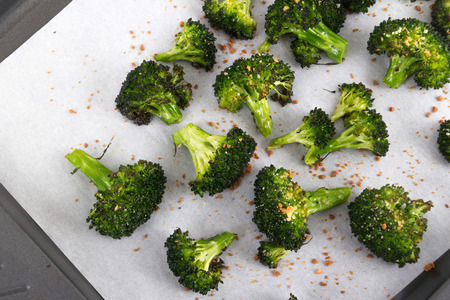 side dish: baked roasted garlic parmesan and olive oil broccoli side dish on wooden table