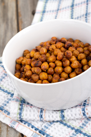 seasoned: Roasted spicy Seasoned Chick Peas healthy snack on wooden table Stock Photo