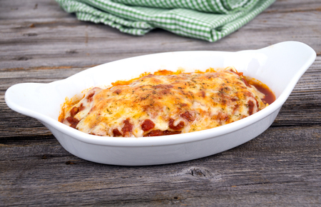 homemade pasta lasagna portion on rustic wood table