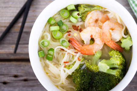 angle view: asian prawn rice noodle soup high angle view closeup on rustic table Stock Photo