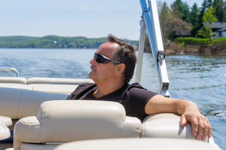 60 years old: men 60 years old relaxing on a boat at summer