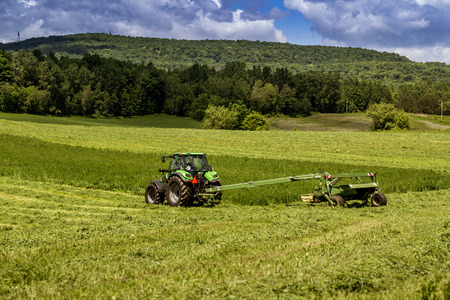 hay field: agriculture tractor machinery harvesting hay field