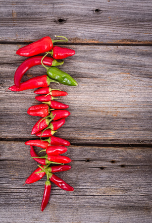various chile hot pepper hanging to dry on wooden wall background