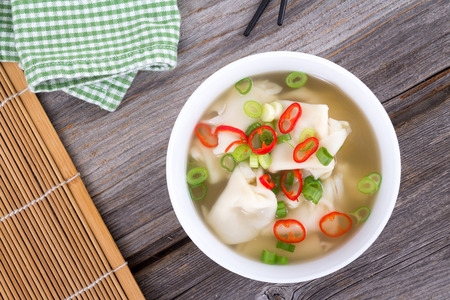 Wonton dumpling asian soup with green onion and thai pepper Stock Photo