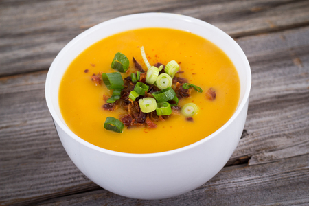 butternut squash soup topped with bacon and green onion on a wooden table Stock Photo