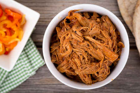 pulled over: bbq pulled pork bowl over a wooden plank table