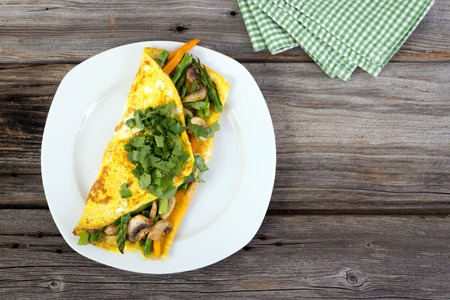 Stuffed vegetable omelet with asparagus, pepper and mushroom on wooden background with cilantro on top