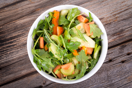 arugula papaya balsamic salad with celery and cucumber over rustic plank table