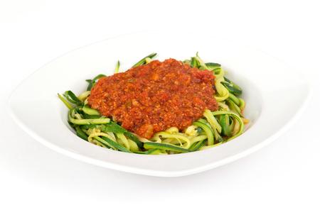 zucchini spaghetti spiral with tomato sauce over white background Фото со стока
