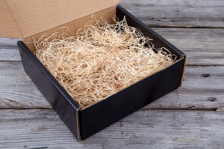 empty product gift box with straw over rustic plank wooden background