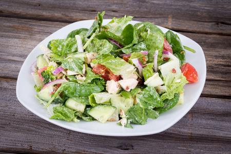 Deliciosa ensalada de pollo y verduras con aderezo ranch sobre mesa de fondo de madera