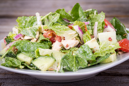 Chicken and vegetables delicious salad with ranch dressing over wooden background table Imagens