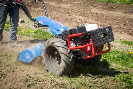 Quebec, Canada-16 may 2018 : Woman worker driving BCS 853 13 HP rototiller is a popular tractor unit preparing soil on outdoor garden Foto de archivo